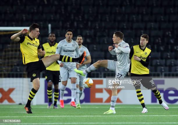 Florian Wirtz of Bayern 04 Leverkusen battles for possession with Cedric Zesiger and Sandro Lauper of BSC Young Boys during the UEFA Europa League...