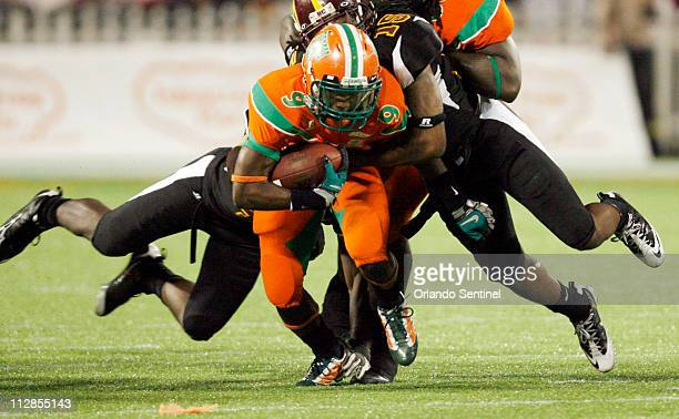 Florida AM wide receiver Antonio Lawrence drags BethuneCookman defenders after a pass reception during the Florida Classic XXI football game at the...