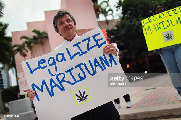 Florida Attorney General candidate Jim Lewis who is running on a platform of legalizing marijuana holds a sign during a campaign rally on October 12...