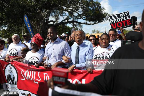 Florida Democratic gubernatorial candidate Andrew Gillum links arms with Reverend Al Sharpton and other supporters for a Souls to the Polls March on...
