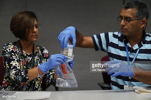 Florida Department of Health workers package up a urine sample to be tested for the Zika virus as they provide people with a free Zika virus test at...