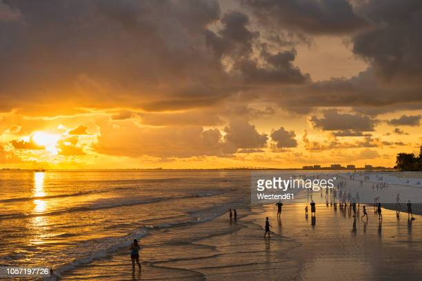 usa, florida, fort myers, silhouettes of fort myers beach and tourists with a huge rain cloud above during sunset - lee county florida stock photos and pictures