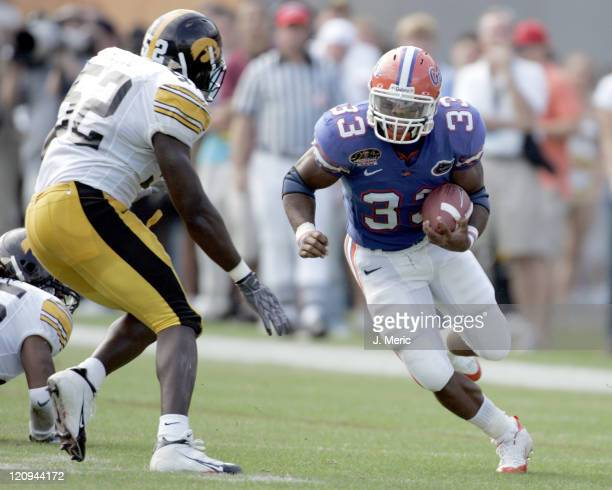 Florida freshman tailback Kestahn Moore looks for some yards as Iowa linebacker Abdul Hodge closes in for the tackle in Monday's Outback Bowl at...