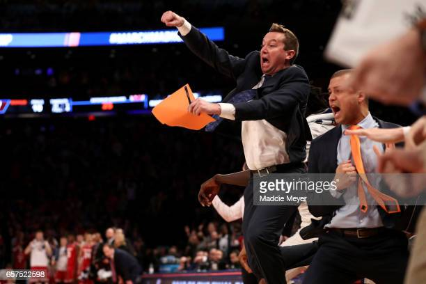 Florida Gators coaches celebrate from the bench after Chris Chiozza of the Florida Gators hit his game winning three point basket in overtime to...