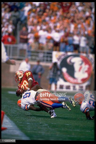 Florida Gators cornerback Anthone Lott tackling Florida State tailback Warrick Dunn and driving him backwards during a game on November 30 1996 in...