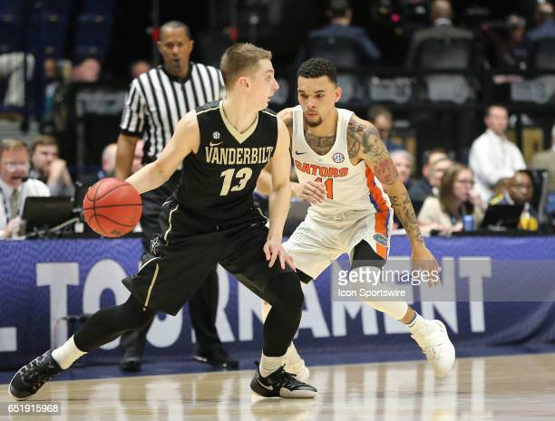 Florida Gators guard Chris Chiozza posts up against Vanderbilt Commodores guard Riley LaChance in OT play of the SEC Basketball Tournament game...
