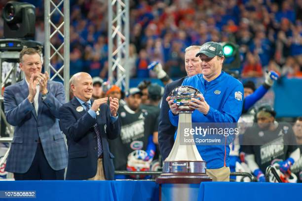Florida Gators head coach Dan Mullen hoists the ChickfilA Peach Bowl trophy with ChickfilA CEO Dan Cathy looking on after the ChickfilA Peach Bowl...