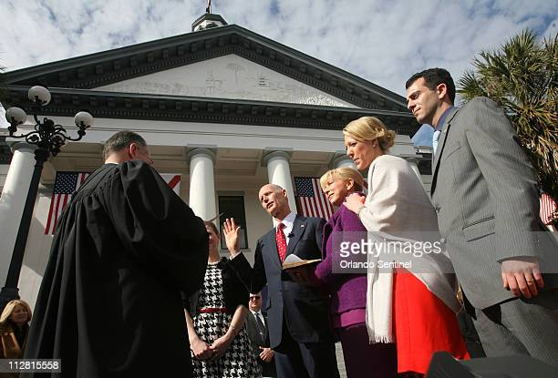 Florida Gov Rick Scott center takes the oath of office at the capitol in Tallahassee Florida Tuesday January 4 2011 Also pictured to the right are...