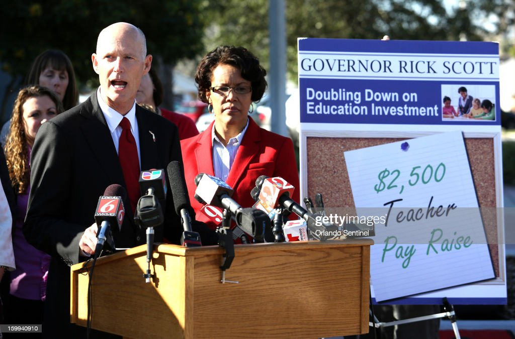 Florida Gov. Rick Scott is joined by Orange County schools superintendent Barbara Jenkins, right, and Ocoee Middle School teachers and administrators for the announcement of the governor's proposal to raise teacher pay statewide in the upcoming state budget, during a news conference at the school in Ocoee, Florida, on Wednesday, January 23, 2013.