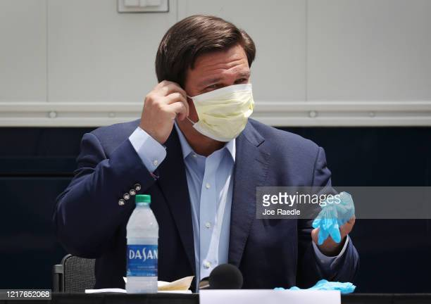 Florida Gov Ron DeSantis prepares to take his face mask before speaking during a press conference at the Miami Beach Convention Center on April 08...
