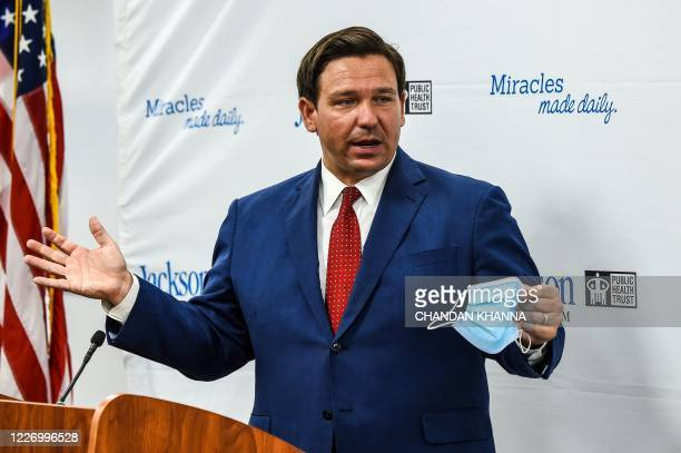 Florida Gov. Ron DeSantis speaks holding his facemask during a press conference to address the rise of coronavirus cases in the state, at Jackson...