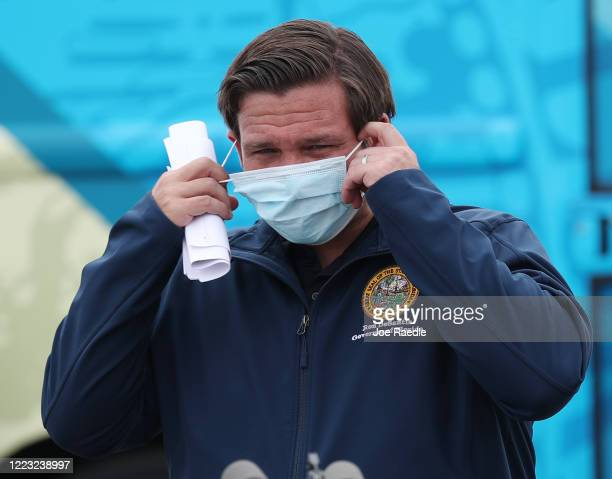 Florida Gov Ron DeSantis takes his mask off as he prepares to speak during a press conference at the Hard Rock Stadium testing site on May 06 2020 in...