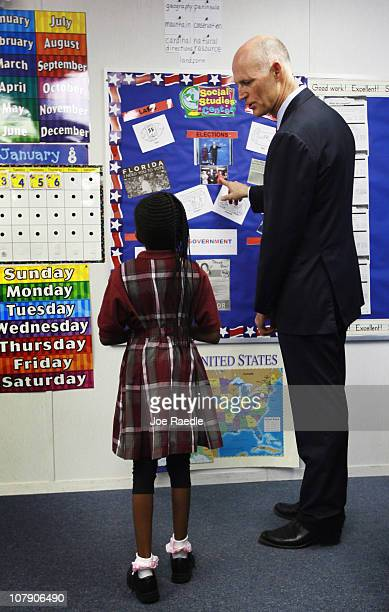 Florida Gov Scott talks with second grader Denisia Purcell about a bulletin board they put up in their classroom featuring a picture of the governor...
