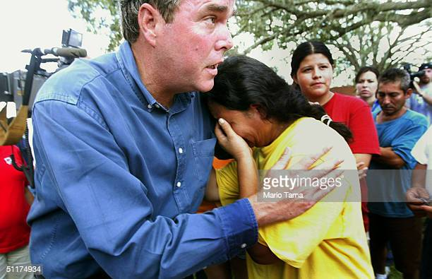 Florida Governor Jeb Bush comforts a grieving woman after he held a news conference August 15 2004 in Arcadia Florida Hurricane Charley destroyed...