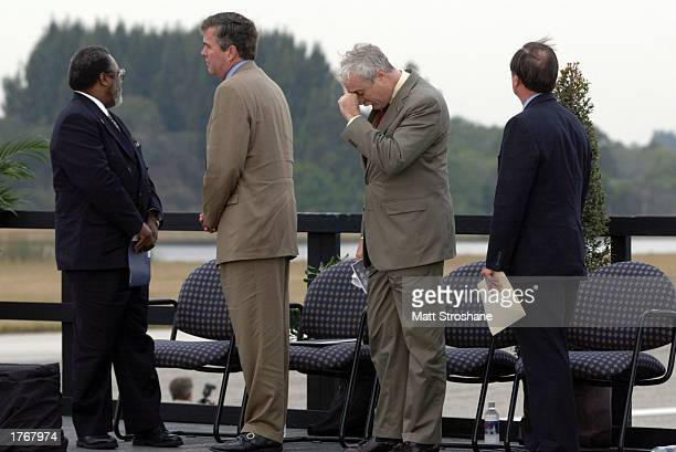 Florida Governor Jeb Bush NASA Administrator Sean O'Keefe and Captain Robert Crippen former KSC director and pilot of Columbia watch the missing man...