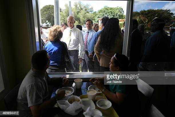 Florida Governor Rick Scott greets people as he attends a road expansion event at the Casa Maiz restaurant where he fielded questions from reporters...
