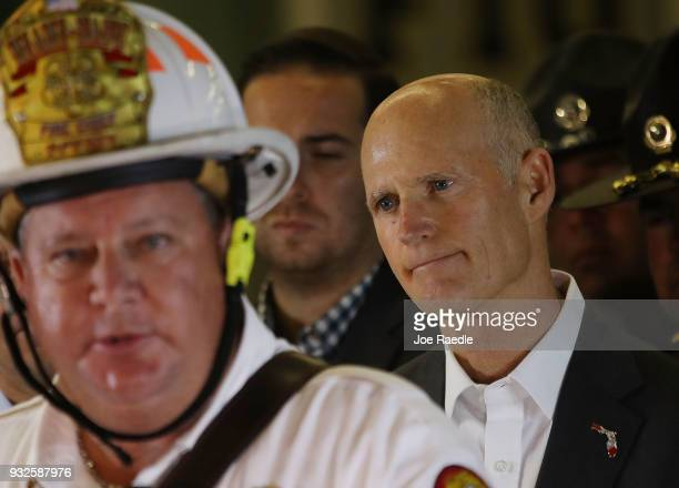 Florida Governor Rick Scott listens as MiamiDade County Fire Chief Dave Downey speaks to the media about a pedestrian bridge near Florida...