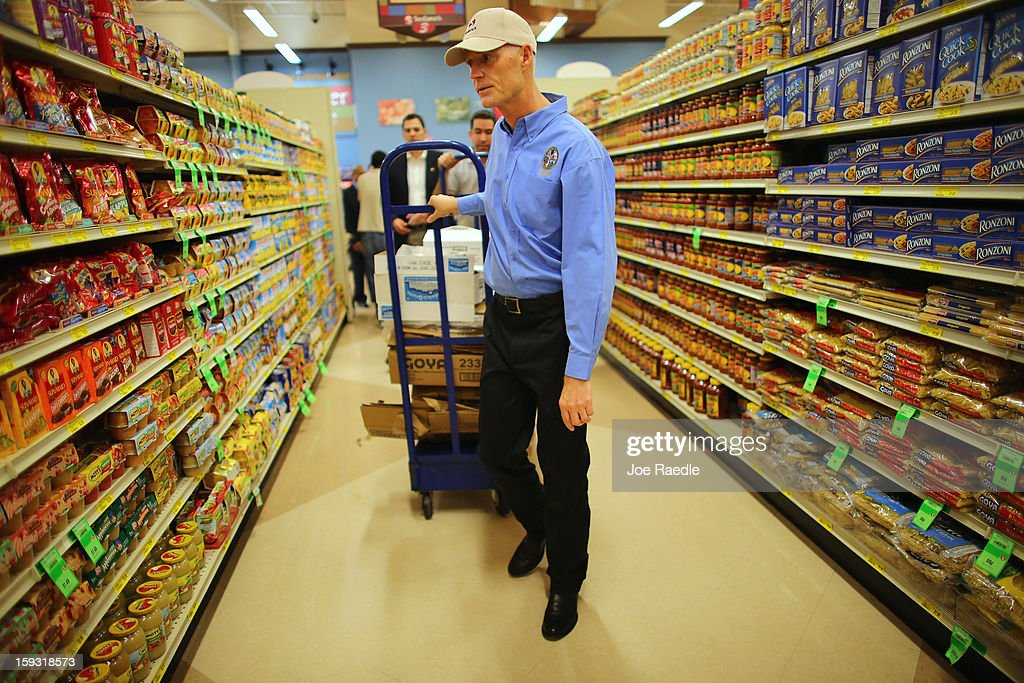Florida Governor Rick Scott pulls Goya products on a cart as he helps stock the shelves at the Sedano's Supermarket on January 11, 2013 in Miami, Florida. Governor Scott spent his 15th 'Let's Get to Work Day' highlighting the importance of building up manufacturing jobs.