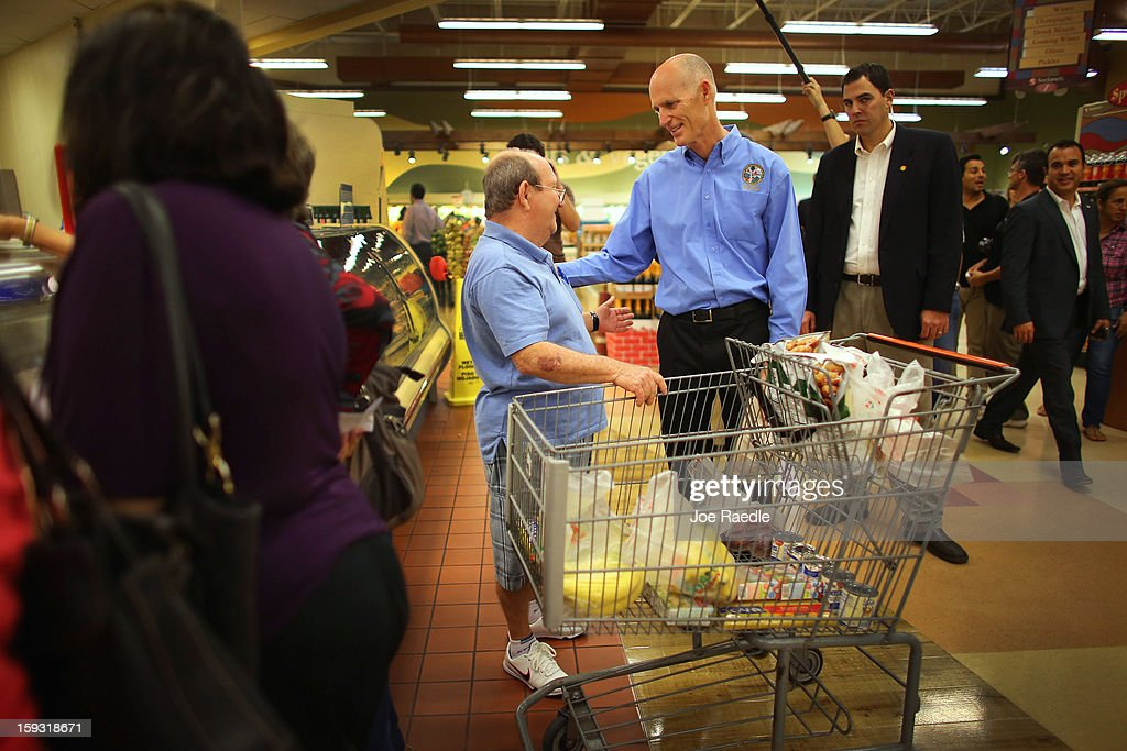 Florida Governor Rick Scott (C) speaks with Roberto Herrarro (L) as he visits Sedano's Supermarket on January 11, 2013 in Miami, Florida. Governor Scott spent part of his 15th 'Let's Get to Work Day' stocking the shelves at the grocery store with Goya products as he highlights the importance of building up manufacturing jobs.