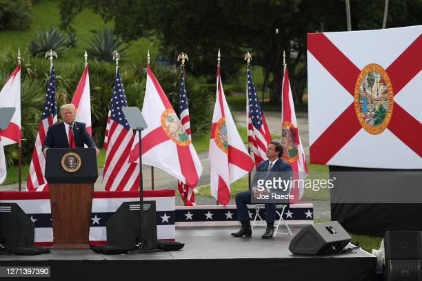 Florida Governor Ron DeSantis listens as President Donald Trump speaks about the environment during a stop at the Jupiter Inlet Lighthouse on...