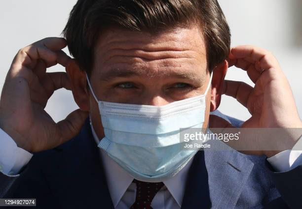 Florida Governor Ron DeSantis places his mask back on after speaking during a press conference about the opening of a COVID-19 vaccination site at...