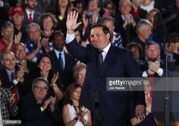 Florida Governor Ron DeSantis waves after speaking about Venezuela before the arrival of President Donald Trump during a rally at Florida...