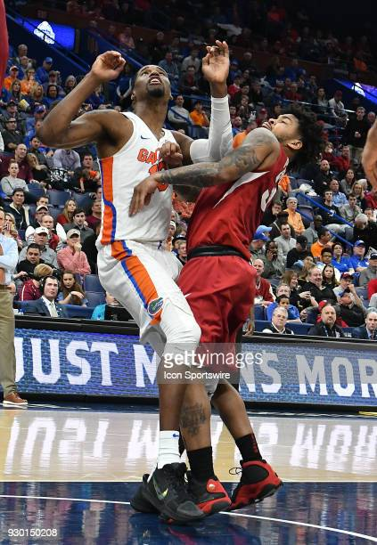 Florida guard Chris Chiozza and Arkansas guard Anton Beard wait to rebound a shot during a Southeastern Conference Basketball Tournament game between...