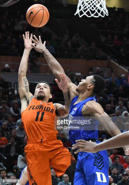 Florida guard Chris Chiozza attempts a shot over Duke guard Gary Trent Jr in the championship game of the Motion Bracket at the PK80Phil Knight...