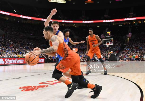 Florida guard Chris Chiozza dribbles baseline against Duke guard Grayson Allen in the championship game of the Motion Bracket at the PK80Phil Knight...