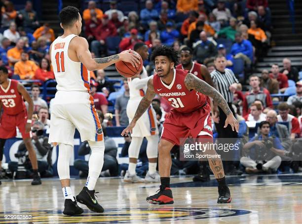 Florida guard Chris Chiozza is closely defended by Arkansas guard Anton Beard during a Southeastern Conference Basketball Tournament game between...