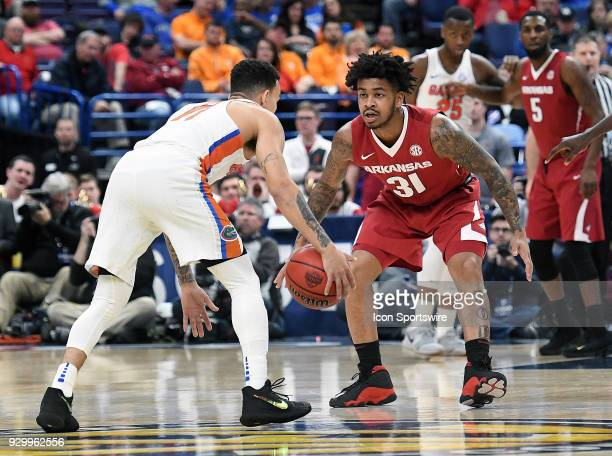 Florida guard Chris Chiozza is closely defended byArkansas guard Anton Beard during a Southeastern Conference Basketball Tournament game between...