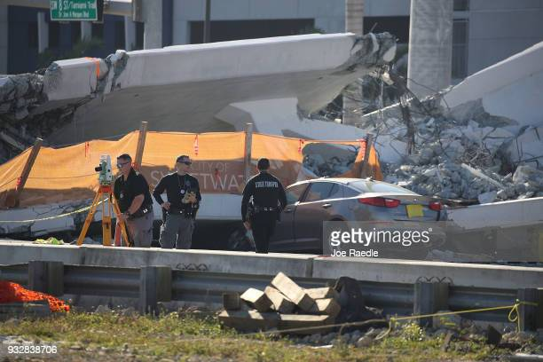 Florida Highway Patrol troopers are seen as they investigate the scene where a pedestrian bridge collapsed a few days after it was built over...