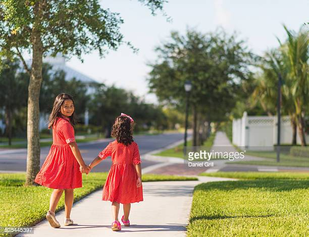 usa, florida, jupiter, back view of girls ( 4-5, 8-9 ) holding hands - orange dress stock pictures, royalty-free photos & images