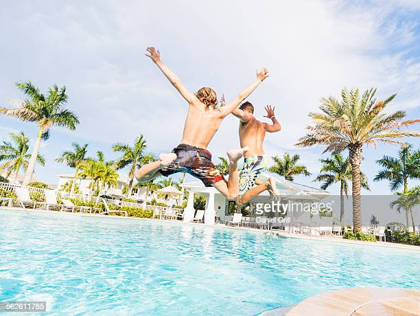 USA, Florida, Jupiter, Boy (8-9) diving into swimming pool with his brother