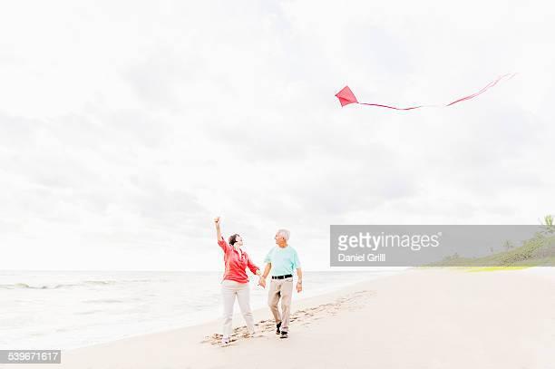 USA, Florida, Jupiter, Couple flying kite together on beach