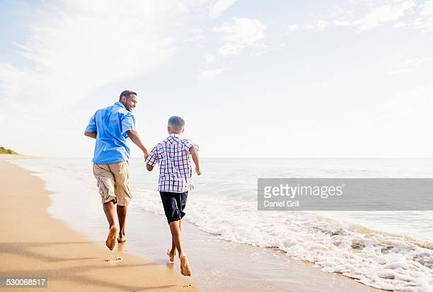 USA, Florida, Jupiter, Father and son (10-11) running on beach