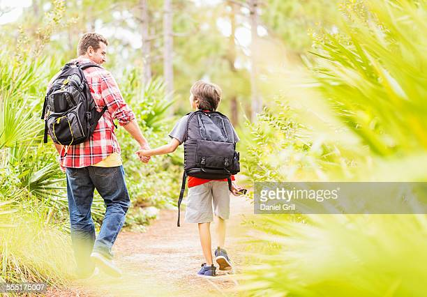 usa, florida, jupiter, father and son (12-13) walking in forest - jupiter florida stock pictures, royalty-free photos & images