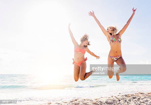 USA, Florida, Jupiter, Female friends jumping on beach