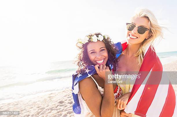 USA, Florida, Jupiter, Female friends on beach with American flag