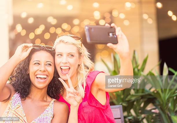 USA, Florida, Jupiter, Female friends taking selfie with smart phone in cafe