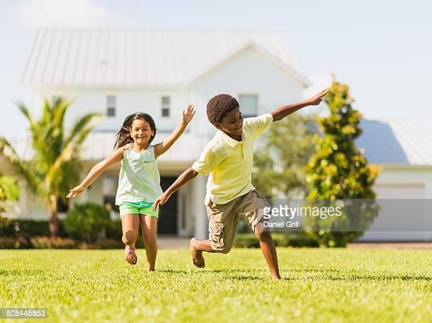 USA, Florida, Jupiter, Girl (8-9) and boy (6-7) playing on front yard
