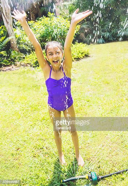 USA, Florida, Jupiter, Girl (8-9) playing in sprinkler