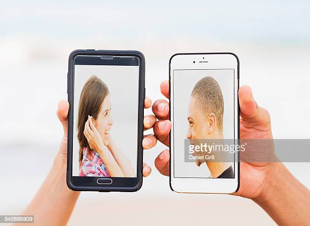 USA, Florida, Jupiter, Hands holding smart phones with pictures of young people