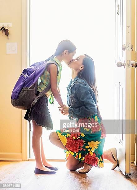 USA, Florida, Jupiter, Mom kissing her daughter (6-7) on goodbye at front door