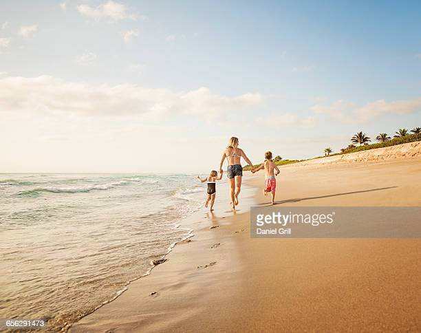 usa, florida, jupiter, mother running with boy (6-7) and girl (4-5) on beach by water - palm beach county stockfoto's en -beelden