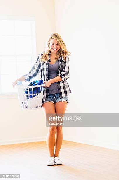 USA, Florida, Jupiter, Portrait of woman holding laundry basket