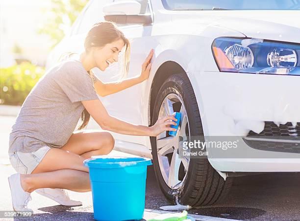 USA, Florida, Jupiter, Portrait of young woman washing white car