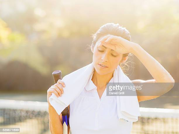 USA, Florida, Jupiter, Portrait of young woman with towel and tennis racket wiping forehead with back of hand