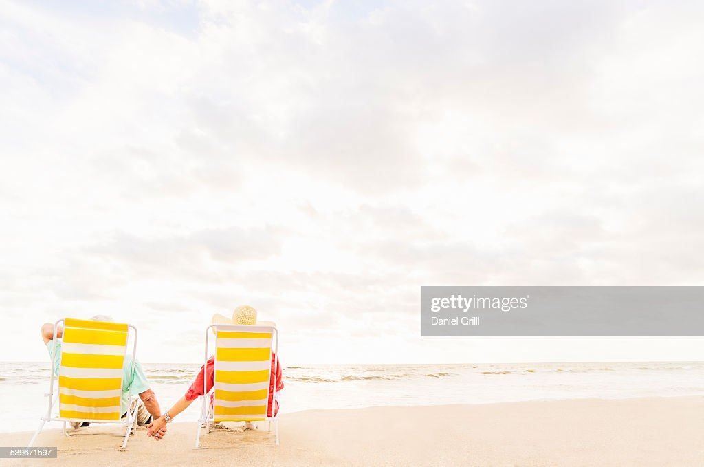 USA, Florida, Jupiter, Rear view of couple sitting in lounge chairs on beach  : Stock Photo