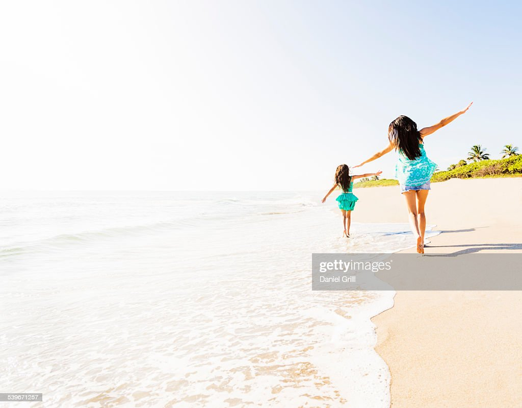 USA, Florida, Jupiter, Rear view of girl (6-7) and her mom running on beach : Stock Photo